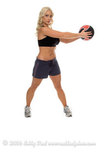 Beautiful young blond woman in shorts and a sports bra working out in the gym with a medicne ball to shape and tone her abs