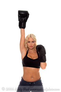 Healthy young woman in black boxing gloves standswith her hand raised in victory after a cardio boxing workout.