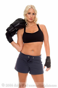 Healthy young woman in hand wraps stands holding her boxing gloves as she prepares for a cardio boxing workout.