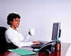 African American business woman typing and drinking a cup of coffee while sitting at her desk in the office