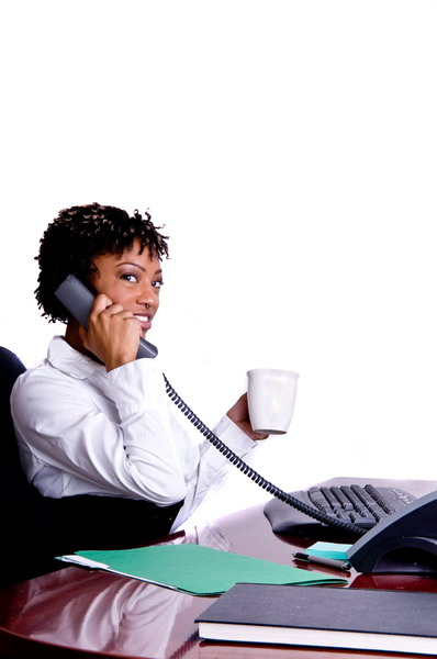 African American business woman talking on the phone and drinking a cup of coffee while sitting at her desk in the office