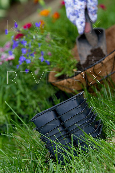 focus on empty flower containers. gardener has planted flowers in coco wire basket in background out of focus.