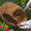 a gardener is adding more potting soil into coco lined hanging basket. preparing for flowers.