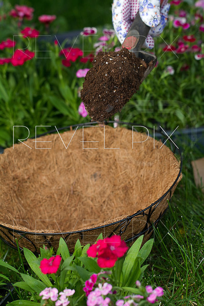a gardener is about to dump some potting soil into an empty coco lined hanging basket