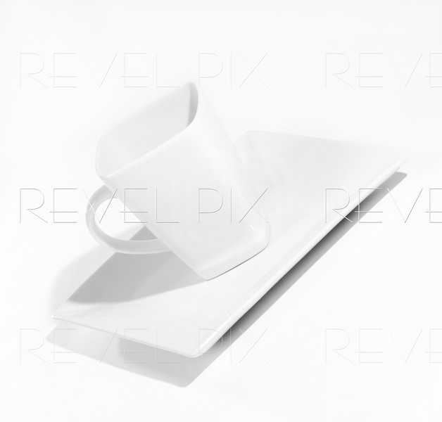 a white coffee cup on a white plate shot on a white background.