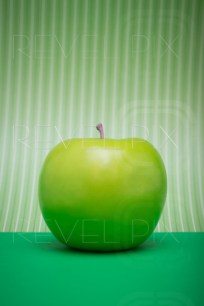 a plastic green apple sits on green ground with a green striped background. copyspace