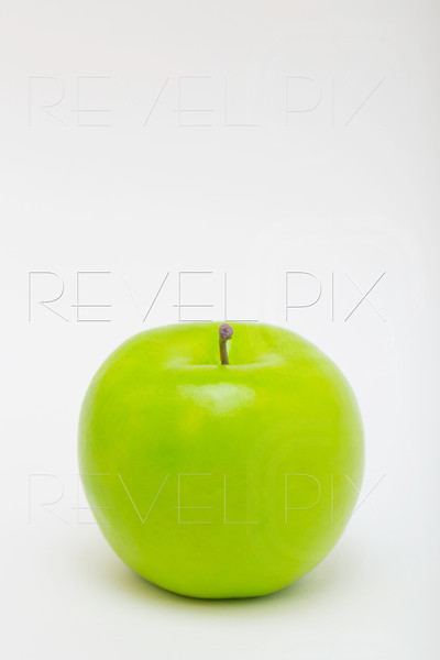 a plastic green apple on a white background. file has clipping path for isolation. copyspace