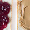 side by side shot. slice of bread with grape jelly and a slice with creamy peanut butter.