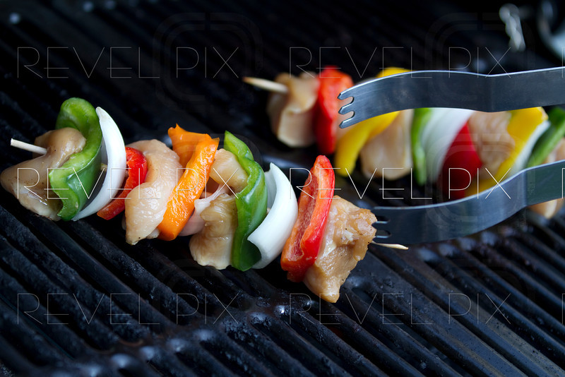 horizontal shot of tongs grabbing a raw chicken kabob on a grill. shallow depth of field