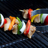 horizontal shot of tongs grabbing a raw chicken kabob on a grill. shallow depth of field