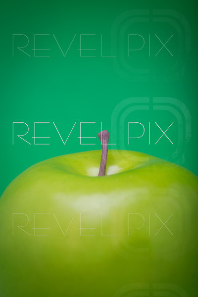 a macro shot of the top of a plastic green apple on a green background. copyspace