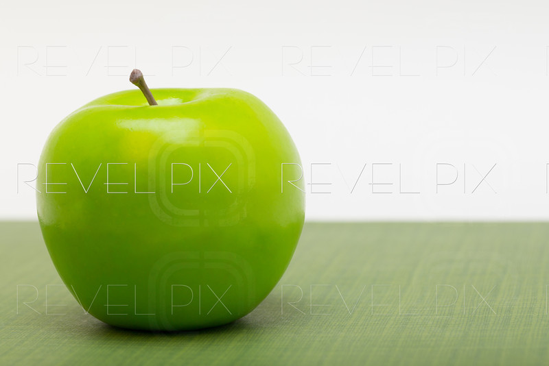 a left justified plastic green apple on patterned ground with a white background. copyspace