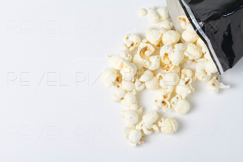 a bag of white cheddar popcorn spills out of a bag. macro shot on white/gray background in studio.