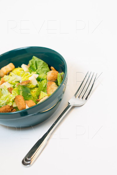 a studio lit shot of a traditional salad with croutons and cheese chunks in a green bowl with a fork on right