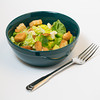 a studio lit shot of a traditional salad with croutons and cheese chunks in a green bowl with a fork