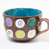 a macro selective shot of a hand painted mug in a studio. focus on front of mug handle