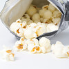 a bag of white cheddar popcorn spills out of a bag. macro shot on white background in studio.