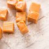 Caramel Cubes and Sea Salt Close Up on White Wood