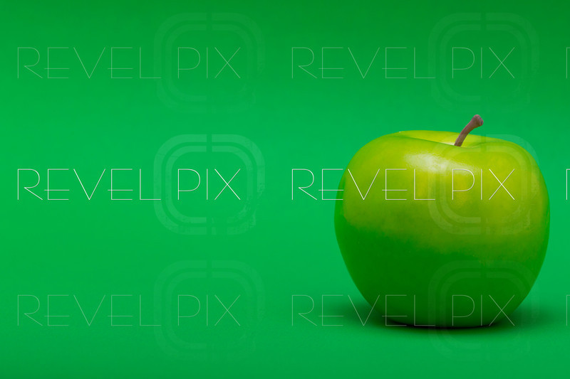 a right justified plastic green apple on a green background. copyspace