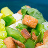 a studio lit macro shot of a traditional salad with croutons and cheese chunks in a green bowl. focus on crouton