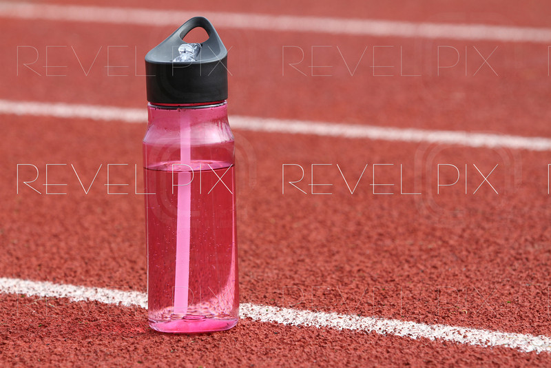a close up shot of a water bottle on a track outside.