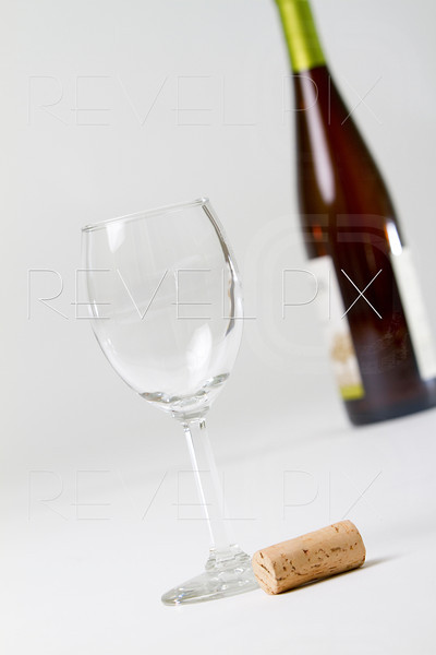a wine glass, cork and blurred wine bottle on a white/gray background