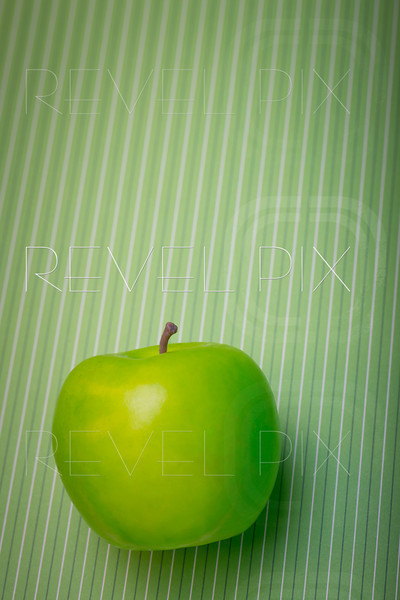 a plastic green apple on a striped green background.