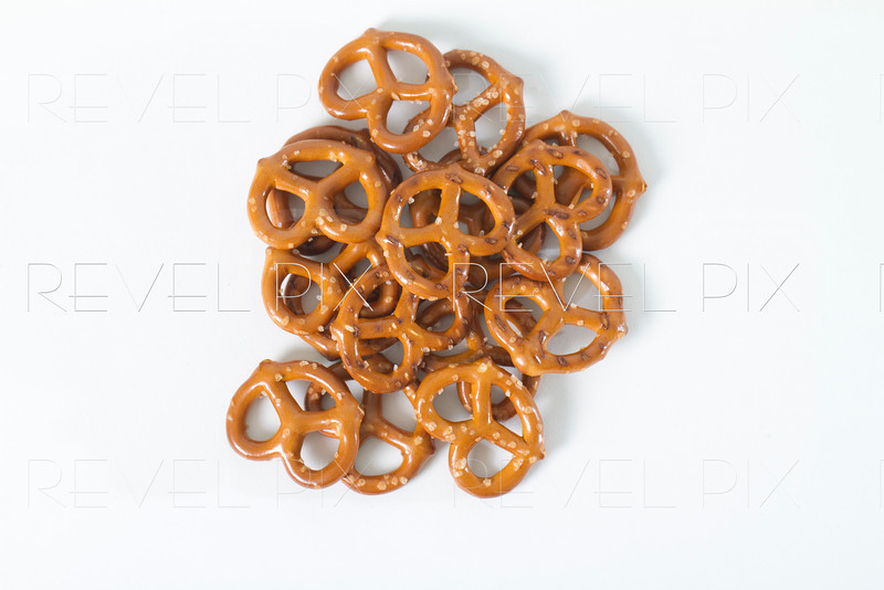 pile of pretzels shot from above on white background.