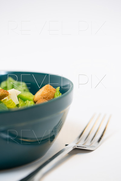 a studio lit shot of a traditional salad with croutons and cheese chunks in a green bowl and fork. with copyspace