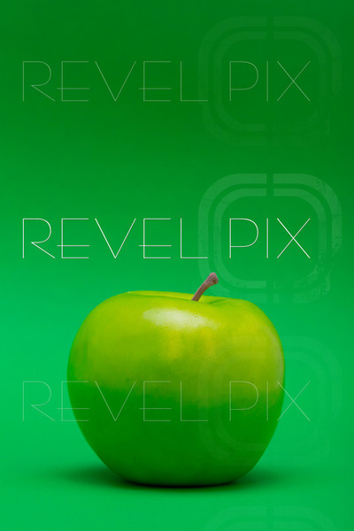 a plastic green apple on a green background.