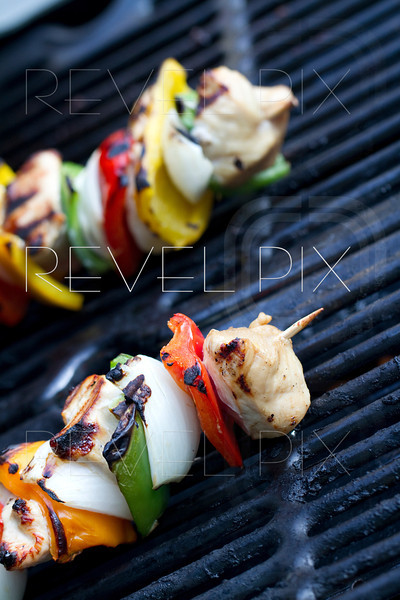 horizontal shot cooked chicken kabob on a grill. shallow depth of field