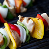 vertical shot of cooked chicken kabob on a grill. shallow depth of field
