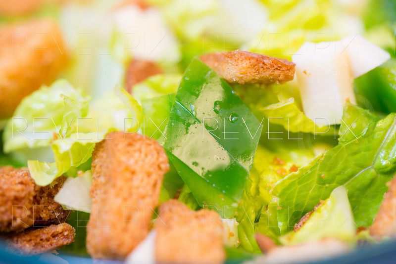 a studio lit shot of a traditional salad with croutons and cheese chunks in a green bowl. focus on water drops on pepper slices