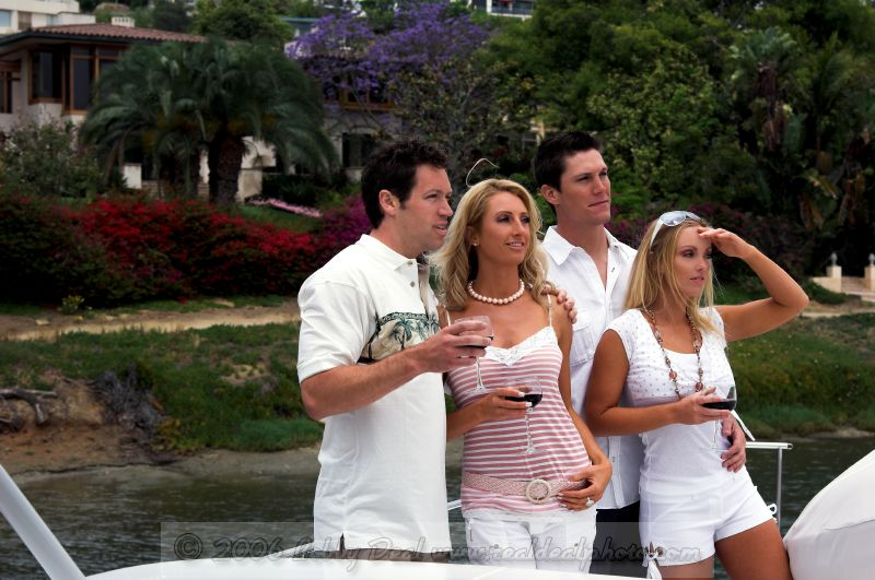 a group of two men and two women celebrating life with a toast  during a yacht party