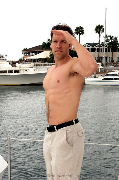 A casual  young man shirtless on a yacht in San Diego harbor