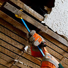 close up of person pulling apart ceiling lathe with crowbar