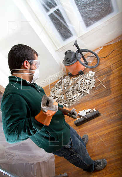 man sweeps debris into a pile. over the shoulder shot with vacuum in corner.