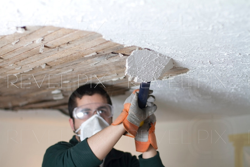man scraping plaster off ceiling lathe, focus on ceiling.
