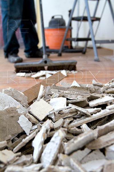 view from rubble. person sweeping plaster rubble into a pile with vacuum and ladder in background.