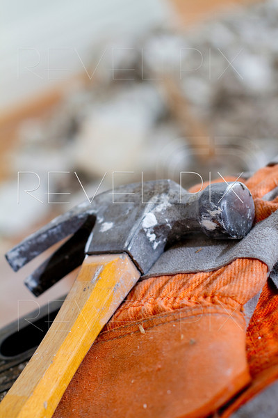a close up shot of a hammer on some work gloves. debris is blurred in the background.