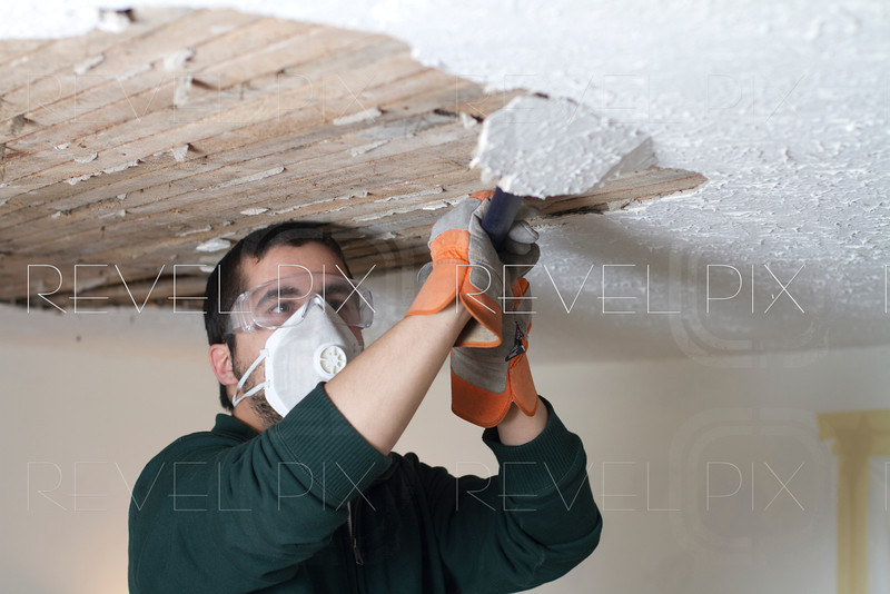 a worker scraping the ceiling and removing plaster from the lathe
