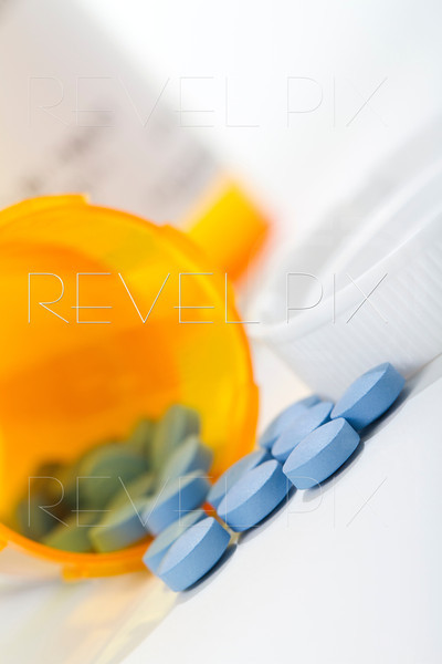 a macro shot of a medicine bottle on its side with pills spilled out. Cap and 2 orange bottle present