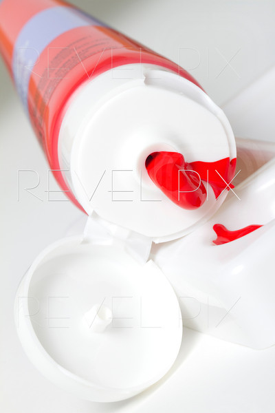 a red paint tube with paint squeezed out into palette.