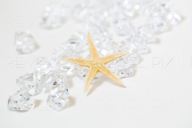 a small yellow starfish rests against a group of plastic gems. macro shot on white background