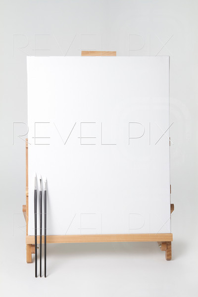"""full shot of canvas on easel with 3 paint brushes leaning up against canvas. Clipping path is of canvas only. Easily place your image on canvas with clipping mask and """"multiply"""" transfer mode to appear below paint brushes."""