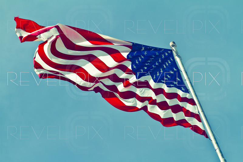 a vintage style photo of the american flag waving on a pole with a vignette against a blue sky.