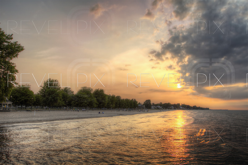 HDR photo of a sunset on the coast of a beach. Trees and people in background