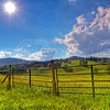 an old fence surrounds a beautiful landscape of rolling green hills and mountains. sun shines down on the lush scene.