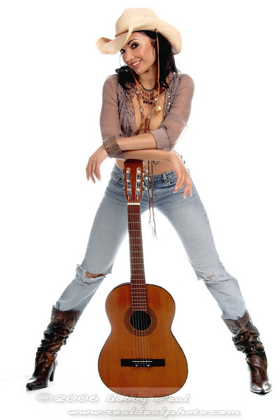 Super sexy rodeo cowgirl in torn jeans, boots and cowboyhat with a nylon string acoustic guitar