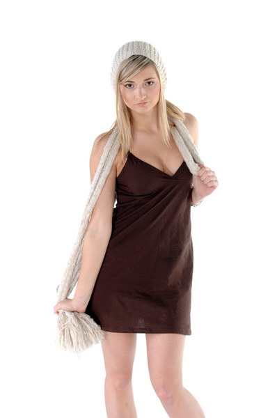 Beautiful young blonde haired , blue eyed fashion model in a in a lowcut dress, knit scarve and cap